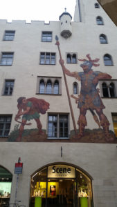 an old-fashioned mural of David and Goliath atop a modern eyewear store